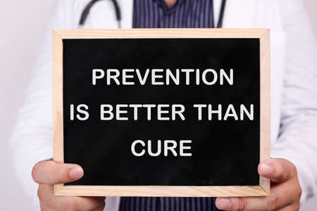 Prevention is better than cure. Male doctor holds chalkboard with health typography quotes written on it. Health and Medical Concept