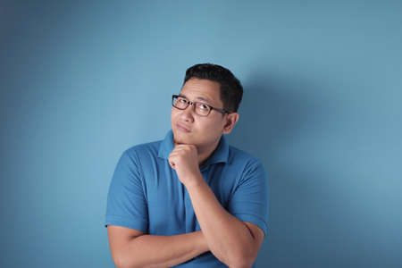 Photo image of young Asian man looked happy, thinking and looking up, having good idea. Half body portrait against blue wall with copy space Reklamní fotografie