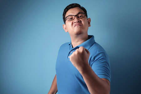 Portrait of funny Asian man showing cynical unhappy angry facial expression putting up his fist challenge to fight, against blue background