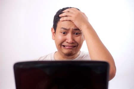 Portrait of young Asian man looked afraid terrified worried when looking at laptop, gasp gesture cant believe what he see on internet Foto de archivo