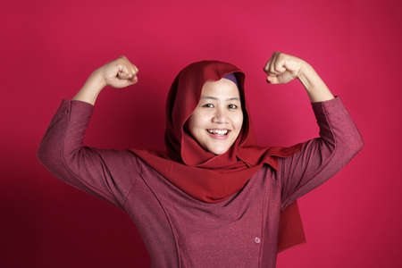 Portrait of Asian muslim lady wearing hijab shows strong muscle power gesture, against red background