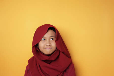 Portrait of young Asian muslim teenage girl wearing red hijab looking up and thinking against yellow background 版權商用圖片