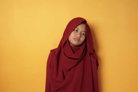 Portrait of sad young Asian teenage muslim girl wearing red hijab looking down and depressed, standing against yellow background