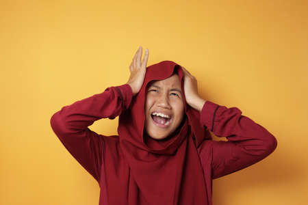 Portrait of teenage Asian muslim girl wearing hijab screaming, showing stress angry expression, against yellow background