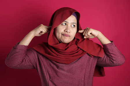 Portrait of Asian muslim lady wearing hijab close hear ears with hands as if do not want to hear something bad, against red background