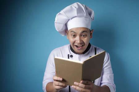 Portrait of Asian male chef reading book of recipes, finding secret recipe, against blue background