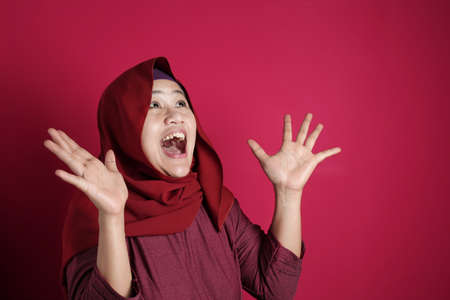 Portrait of happy muslim woman celebrating victory, winning gesture smiling and greeting something from above with copy space concept