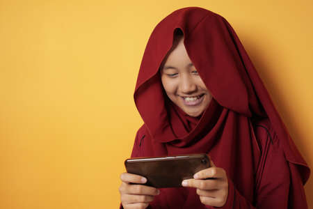 Portrait of cute beautiful Asian muslim teenage girl wearing hijab playing online games on phone, young girl happy and excited doing leisure activity, against yellow background