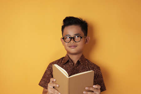 Smart little Asian boy student reading book and thinking, looking up and smiling, against yellow background with copy space