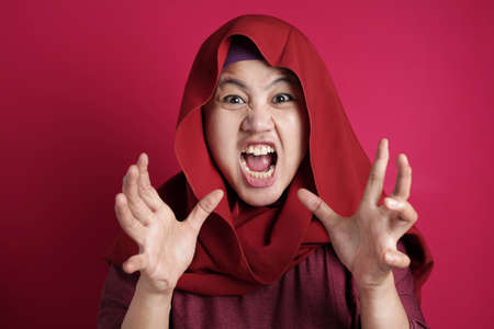 Portrait of Asian muslim lady wearing hijab shows angry screaming gesture, against red background