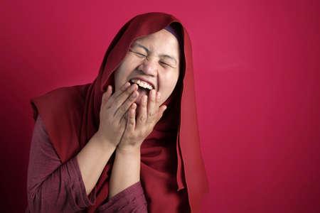 Portrait of muslim lady wearing hijab laughing hard, happy expression, close up head shot against red bakcground Zdjęcie Seryjne