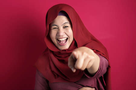 Portrait of muslim lady wearing hijab laughing hard, happy expression, close up head shot against red bakcground 스톡 콘텐츠
