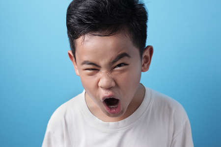 Portrait of angry Asian boy screaming loud, naughty rebel schoolkid concept