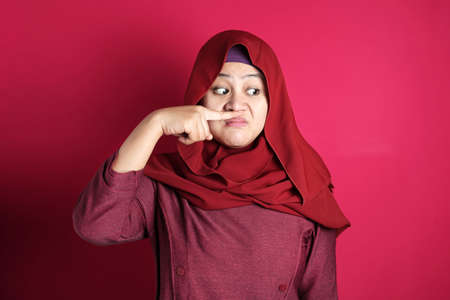 Portrait of cute funny Asian muslim lady wearing hijab close her nose because of bad disgusting smell odor, against red background Фото со стока