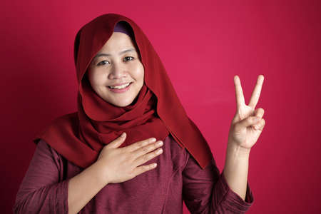 Portrait of happy Asian muslim woman wearing red hijab making pledge gesture, hand on chest holding heart, making promise concept