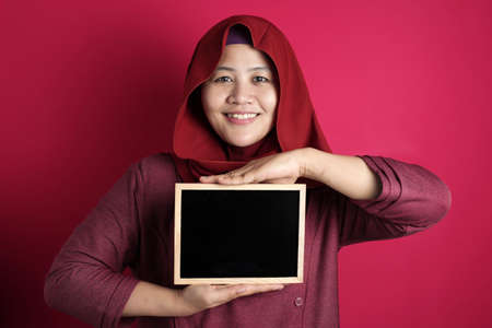 Portrait of smart happy successful Asian muslim woman wearing hijab smiling at camera while holding and showing empty blackboard or chalk board against red background, copy space