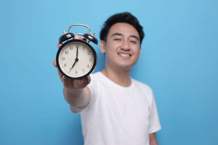 Young Asian man wearing shite shirt shows time on clock with a happy expression, time management. Half body portrait against blue background Фото со стока