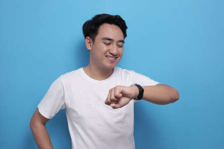 Young Asian male student man checking time on his wristwatch and smiling, happy expression, against blue background