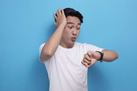 Portrait of funny Asian man shocked worried to see his wrist watch, late time concept