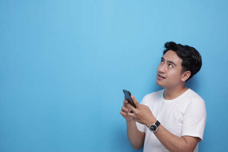 Young Asian man smiling, thinking and looking up while chat messaging on his smart phone, half body side view portrait over blue background with copy space
