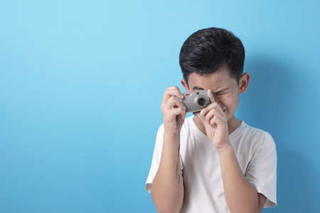 Happy Asian boy doing photography leisure activity, kid as photographer taking picture with his digital camera, against blue background Banco de Imagens - 138239298