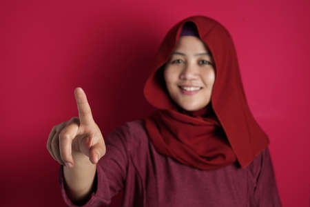 Portrait of Asian muslim woman smiling happily with finger pointing or touching virtual screen against red background, number one sign copy space template Standard-Bild
