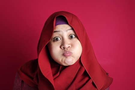 Retrato de mujer musulmana asiática soplando o hinchando su mejilla, expresión de sorpresa