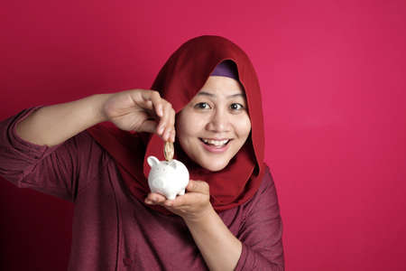 Young happy successful Asian businesswoman put coin into piggy bank in hand, future saving investment concept, red background