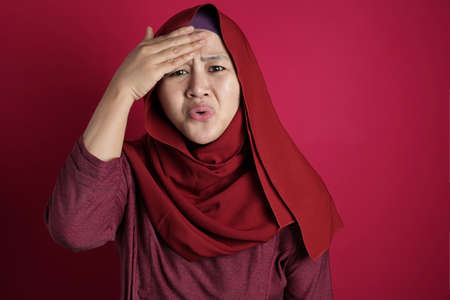 Portrait of young Asian muslim woman wearing hijab shows regret gesture, hand on her forehead, forget something important, against red background