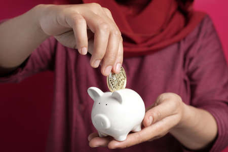 Female putting physical bitcoin into piggy bank, investment in cryptocurrency concept Stock Photo
