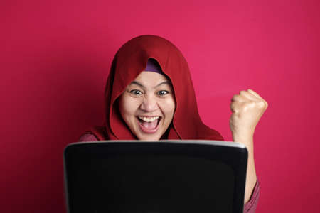 Asian Muslim women using hijab look surprised and happy to see good news received online in an email, women showing expressions of victory in front of their laptops, red background