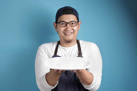 Portrait of Asian male chef or waiter looks happy and proud presenting something on his empty white plate, copy space meal menu concept