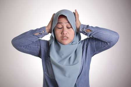 Portrait of Asian muslim lady wearing hijab close hear ears with hands as if do not want to hear something bad