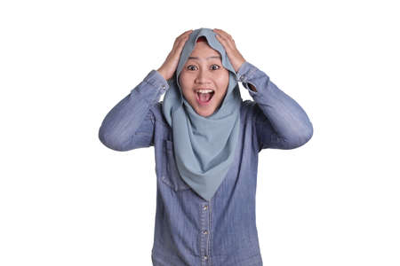 Portrait of cute young Asian muslim lady wearing hijab shows surprised or shocked expression with open mouth, close up facial expression isolated on white