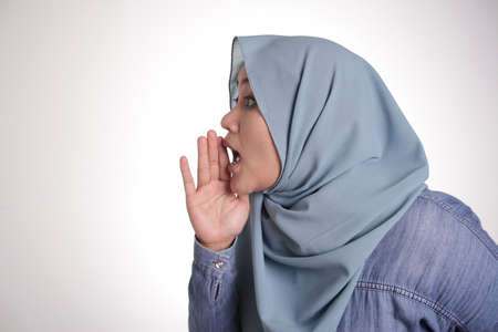 Portrait of Asian muslim lady wearing  hijab tells something secret, whispering gesture, gossip hoax news concept
