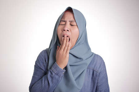 Portrait of tired sleepy Asian muslim lady yawning, lazyness overworked concept