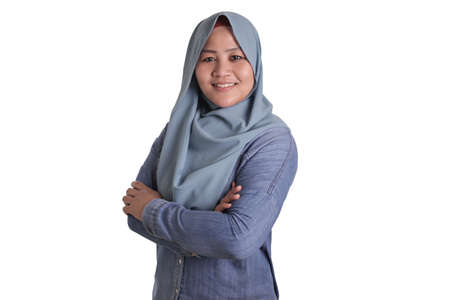 Portrait of Asian muslim woman wearing hijab smiling friendly with crossed arms, confident gesture, successful businesswoman