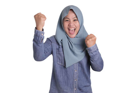 Portrait of success beautiful Asian muslim woman wearing hijab showing winning victory gesture isolated on white