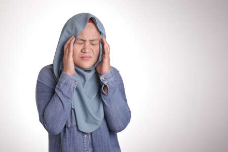Portrait of Asian muslim lady wearing hijab hold her head in pain for having headache, isolated on white