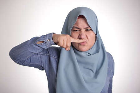 Portrait of cute funny Asian muslim lady wearing hijab close her nose because of bad disgusting smell odor 스톡 콘텐츠