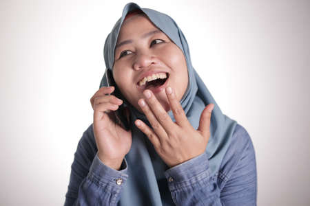 Portrait of muslim lady wearing hijab talking on phone, happy smiling expression having good news, isolated on white