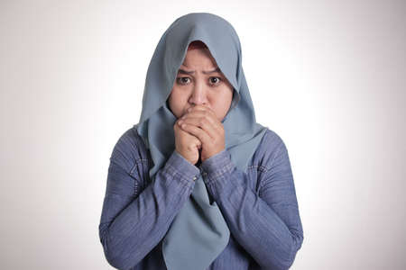 Close up portrait of Asian muslim woman wearing hijab closing her mouth with fingers. Worried gesture, cant say anything. Holding breath waiting for something important 스톡 콘텐츠
