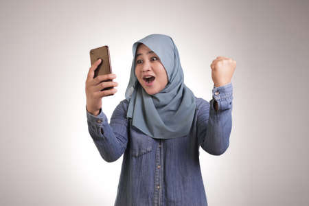 Portrait of young Asian muslim woman wearing hijab get good news on her phone, happy surprised expression 스톡 콘텐츠
