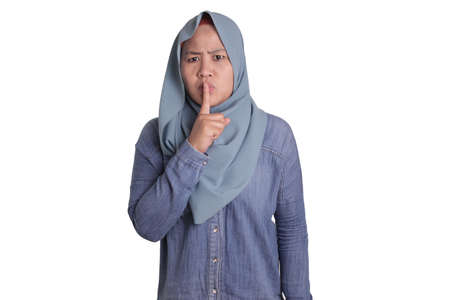Portrait of Asian muslim lady wearing hijab shushing gesture, put her finger on lips telling secretly gossip concept, isolated on white 스톡 콘텐츠