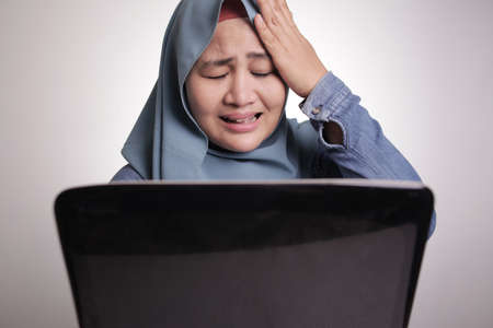 Sad muslim businesswoman crying expression to see bad financial report on laptop, loss in stock market concept, watching sad movies online streaming