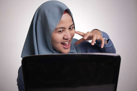 Portrait of Asian muslim woman with cunning look working on laptop, hacker internet criminal concept 스톡 콘텐츠
