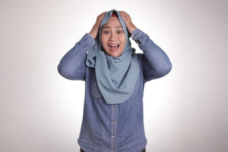 Portrait of beautiful Asian muslim woman wearing hijab shocked worried with mouth opened, isolated on white