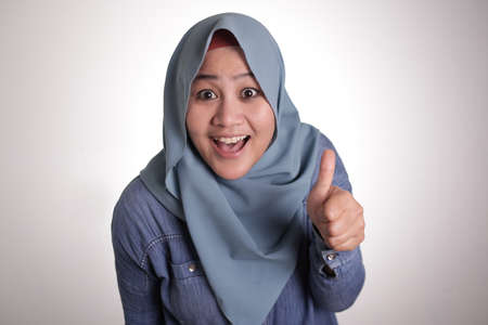 Portrait of young Asian muslim lady wearing hijab shows thumbs up gesture, smiling happy face, approved OK sign 스톡 콘텐츠