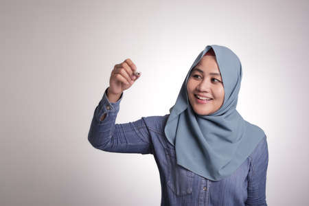 Portrait of young beautiful Asian muslim woman writing something in the air or virtual screen, smiling happy expression 스톡 콘텐츠