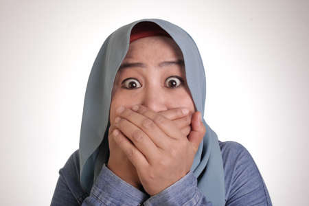 Portrait of Asian muslim woman wearing hijab closing her mouth with fingers. Worried gesture, cant say anything. Shocked surprised to hear bad news or gossip